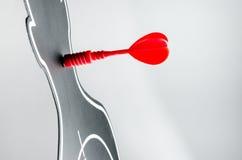 Красная стрелка на доске дротика в форме профиля на серой предпосылке Стоковые Изображения