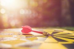 Красная стрелка дротика в центре dartboard Нерезкость и bokeh в солнце Стоковое фото RF