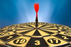 Красная стрелка дротика ударяя в центре цели dartboard Стоковые Изображения