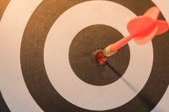 Красная стрелка цели дротика ударяя на яблочке с светом солнца Стоковые Изображения