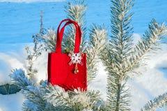 Красная сумка подарка с снежинкой из ткани на ветви покрытой с снегом, зиме сосны, праздничная предпосылка рождества, Стоковые Фото