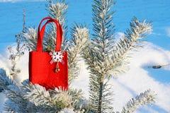 Красная сумка подарка с снежинкой из ткани на ветви покрытой с снегом, зиме сосны, праздничная предпосылка рождества, Стоковое фото RF