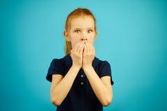 Красная с волосами девушка с большими глазами страха предусматривала рот с руками против голубой предпосылки стоковая фотография rf