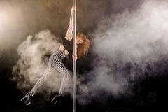 Красная с волосами сексуальная девушка танца поляка работает и представляет на опоре в дыме Стоковое Изображение