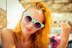 Красная с волосами женщина в кафе пляжа Стоковое Изображение RF