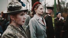 Красная с волосами женщина в ретро шляпе и пальто на историческом событии в городе паркуют видеоматериал