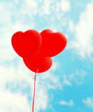 Красная форма сердца воздушных шаров летая над голубым небом Стоковая Фотография