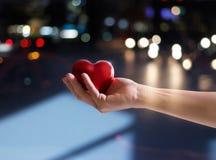 Красная форма сердца в руке женщины на улице на ноче, дне валентинки Стоковые Фотографии RF