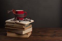 Красная чашка предусматриванная в шарфе, открытой книге и стеклах, космосе экземпляра стоковое изображение