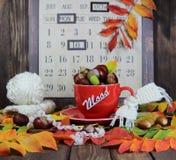 Красная чашка с связанным шарфом, каштанами и жолудями на фоне календаря осени с настроением надписи Стоковое фото RF