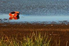 Красная шлюпка на спокойном озере стоковая фотография