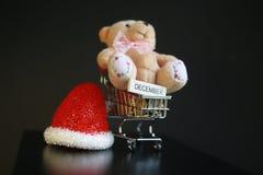 Красная шляпа рождества, монетки в миниатюре вагонетки и милая игрушка плюшевого медвежонка изолированная на черной темной предпо Стоковые Фото