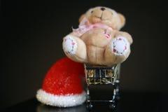 Красная шляпа рождества, монетки в миниатюре вагонетки и милая игрушка плюшевого медвежонка изолированная на черной темной предпо Стоковые Изображения