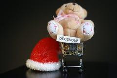 Красная шляпа рождества, монетки в миниатюре вагонетки и милая игрушка плюшевого медвежонка изолированная на черной темной предпо Стоковая Фотография RF