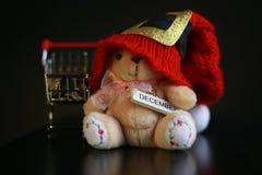 Красная шляпа рождества, монетки в миниатюре вагонетки и милая игрушка плюшевого медвежонка изолированная на черной темной предпо Стоковое фото RF
