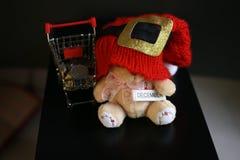 Красная шляпа рождества, монетки в миниатюре вагонетки и милая игрушка плюшевого медвежонка изолированная на черной темной предпо Стоковое Изображение RF