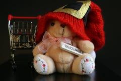 Красная шляпа рождества, монетки в миниатюре вагонетки и милая игрушка плюшевого медвежонка изолированная на черной темной предпо Стоковая Фотография