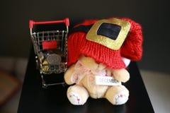 Красная шляпа рождества, монетки в миниатюре вагонетки и милая игрушка плюшевого медвежонка изолированная на черной темной предпо Стоковое Изображение