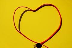Красная multi форма сердца кабеля заряжателя на желтой предпосылке стоковая фотография rf