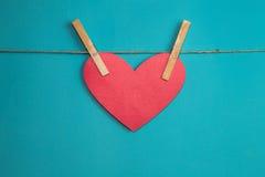 Красное бумажное сердце прикрепленное к веревочке с деревянными штырями Стоковое Изображение