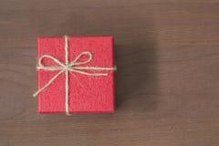 Красное взгляд сверху смычка подарка на деревянной предпосылке с космосом экземпляра Стоковые Изображения