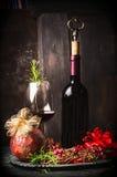 Красное вино в кубке и бутылке с праздничным украшением рождества на темной деревянной предпосылке Стоковое Изображение