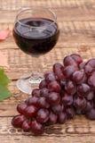 Красное вино в стекле с красными виноградинами Стоковое Изображение RF