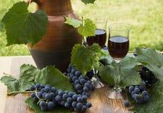 Красное вино в stemware стоя на деревянной предпосылке с виноградинами и листьями зеленого цвета Стоковые Изображения