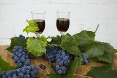 Красное вино в stemware стоя на деревянной предпосылке с виноградинами и листьями зеленого цвета Стоковое фото RF