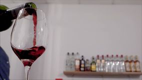 Красное вино завихряясь в стеклянном замедленном движении видеоматериал