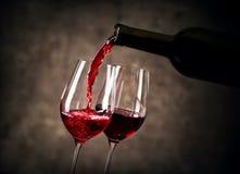 Красное вино лить в стекло от бутылки стоковые фотографии rf