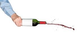 Красное вино лить из бутылки, который держат вручную Стоковые Фото