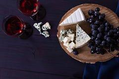 Красное вино и закуски Вино, виноградины, сыр, гайки, оливки Романтичный вечер, натюрморт Стоковое фото RF