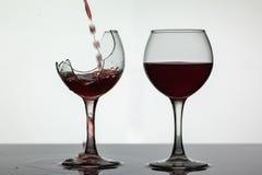 Красное вино лить в сломленный бокал на влажной поверхности Розовое вино льет стоковая фотография