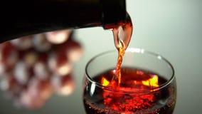 Красное вино полито в стекло на светлой предпосылке сток-видео