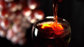 Красное вино полито в стекло на темной предпосылке акции видеоматериалы