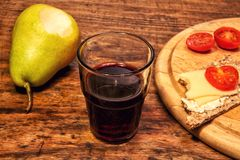 Красное вино с грушей и хлебом на деревянном столе Стоковое фото RF