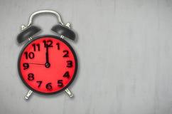 Красное время обеда будильника на серой предпосылке цемента Стоковая Фотография