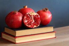 Красное гранатовое дерево на куче книг Стоковая Фотография RF
