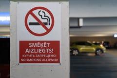 Красное для некурящих allower подписывает в 3 языках в подземной стоянке с автомобилями видимыми на заднем плане стоковое фото