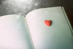 Красное декоративное сердце на открытой книге Стоковые Изображения