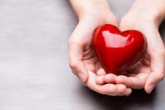 Красное деревянное сердце в руках ребенка Стоковые Изображения RF
