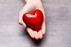 Красное деревянное сердце в руках ребенка Стоковое Изображение RF