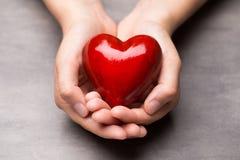 Красное деревянное сердце в руках ребенка Стоковое Фото