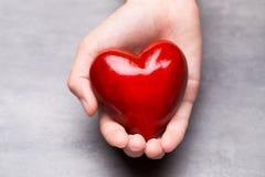 Красное деревянное сердце в руках ребенка Стоковое фото RF