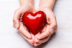 Красное деревянное сердце в руках ребенка Стоковые Изображения