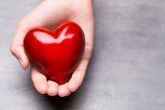 Красное деревянное сердце в руках ребенка Стоковая Фотография