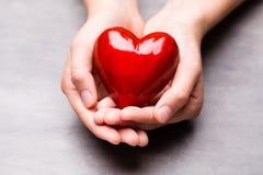 Красное деревянное сердце в руках ребенка Стоковые Фото