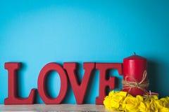 Красное деревянное слово Любовь Свеча с желтыми цветками Стоковые Фото