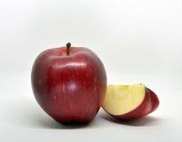 Красное желтое яблоко с зелеными лист и куском стоковое изображение